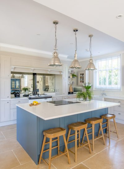 Kitchen with island and wooden stools, three pendant lights and silver fridge
