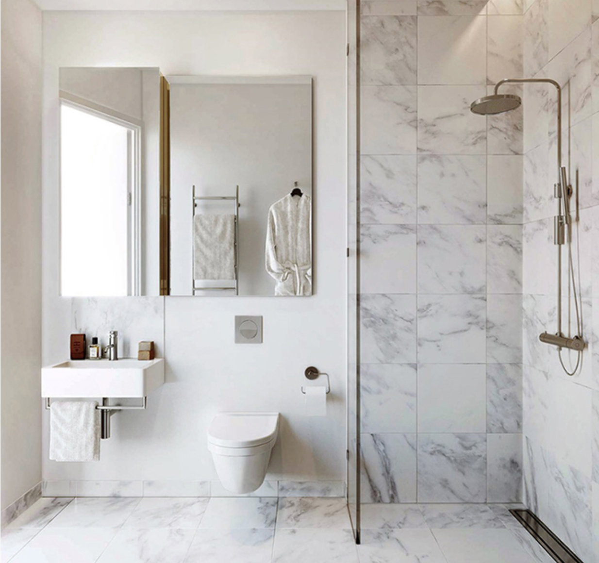 White and grey wet room with marble tiled shower stall and floor, rain head shower, wall hung toilet and sink unit