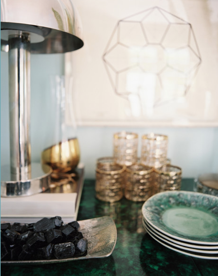 Mixed metals on tabletop - a chrome lamp, hammered silver dish and golden framed glasses